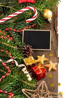 Composición de navidad con una pequeña pizarra en madera marrón de cerca con espacio de copia