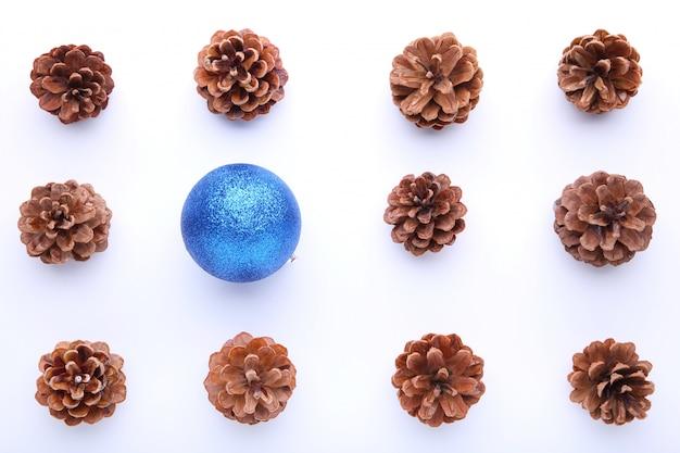 Composición de navidad con piñas y bolas de navidad azul sobre fondo blanco.