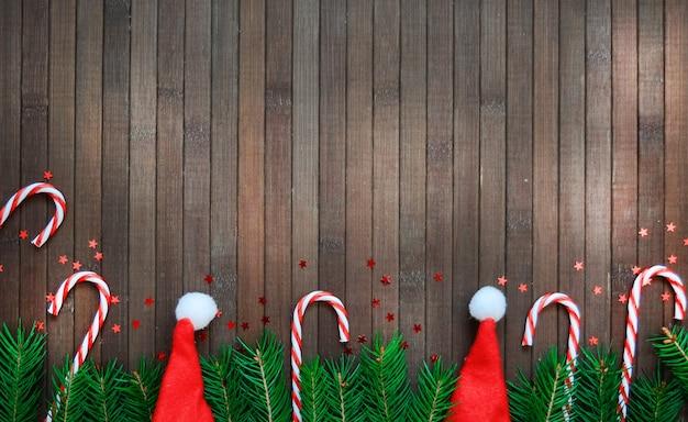 Composición de navidad de una rama de árbol, sombrero de santa, estrellas de caramelo, piña, en patrón de vacaciones de año nuevo de madera. copyspace