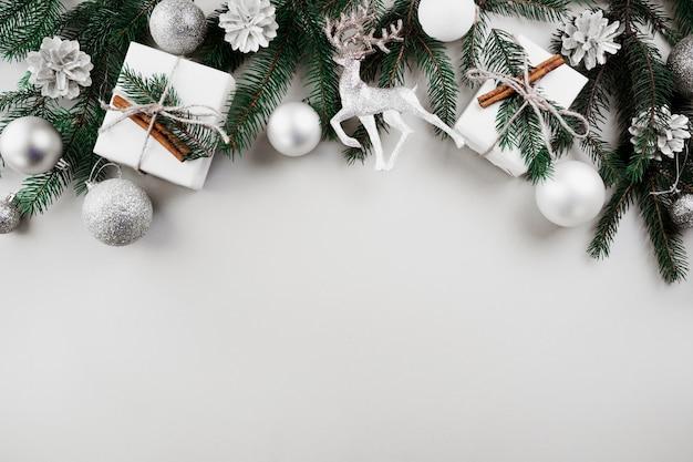Composición de navidad de ramas de abeto verde con adornos de plata