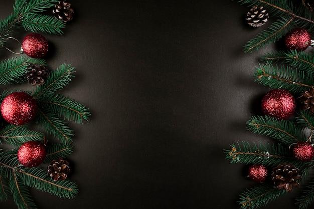 Composición de navidad de ramas de abeto verde con adornos rojos