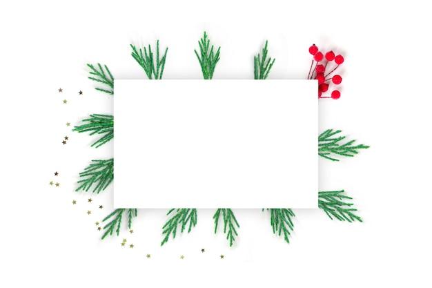 Composición de navidad ramas en blanco de un árbol de navidad estrellas doradas bayas rojas sobre un fondo blanco