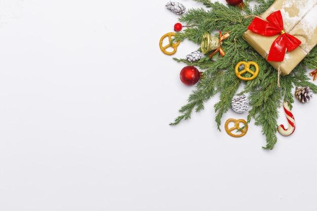 Composición de navidad de ramas coníferas, decoraciones y dulces sobre fondo claro. endecha plana. vista superior concepto de año nuevo de naturaleza. copia espacio
