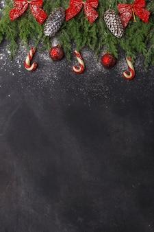 Composición de navidad de ramas coníferas, decoraciones y dulces sobre fondo oscuro. endecha plana. vista superior concepto de año nuevo de naturaleza. copia espacio