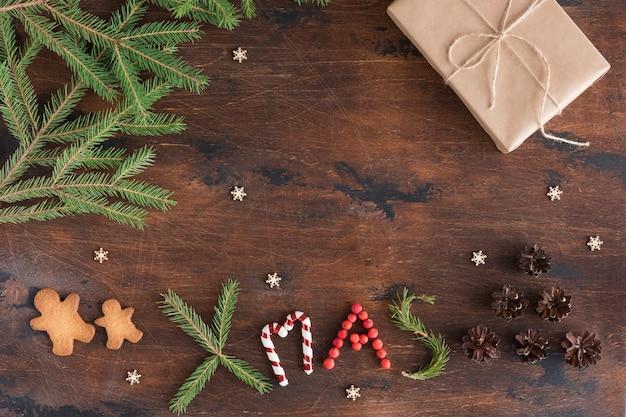 Composición de navidad con regalo y hombre de jengibre en madera oscura.