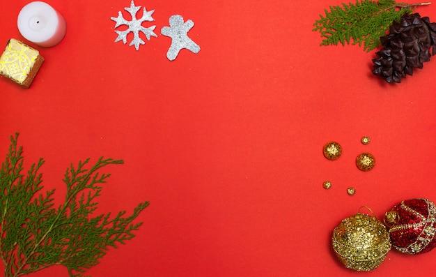Composición de navidad regalo de navidad, conos de pino, ramas de abeto sobre fondo rojo