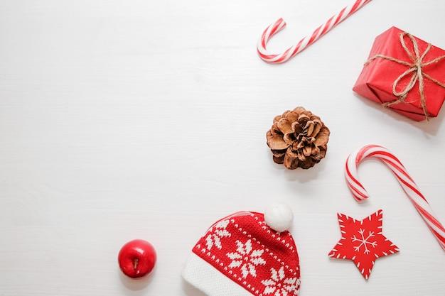Composición de navidad regalos, conos de abeto, decoraciones rojas sobre fondo blanco.