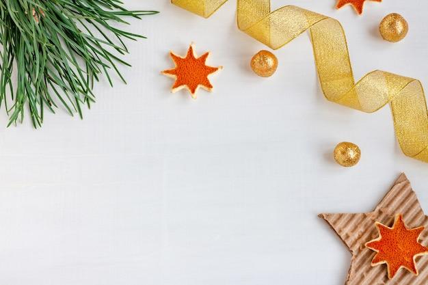 Composición de navidad sobre un fondo de madera blanca de ramas de pino, bolas de oro, cintas y estrellas