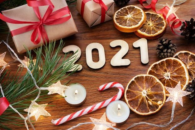 Composición de navidad sobre un fondo de madera oscura con regalos, juguetes y una guirnalda, vista superior.