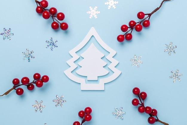 Composición navideña con abeto blanco, bayas de acebo y copos de nieve sobre fondo azul pastel