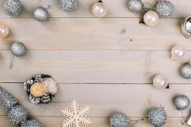 Composición navideña de adornos de plata con vela.