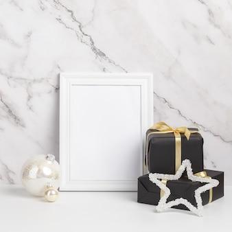 Composición navideña. adornos y regalos de navidad enmarcados en blanco sobre un fondo de mármol