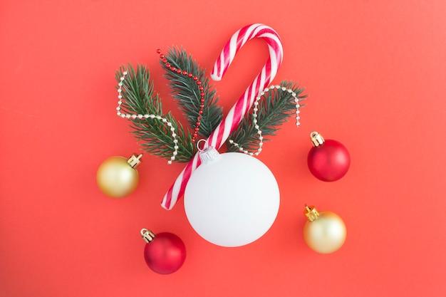 Composición navideña con bola blanca, ramas de abeto y caña de caramelo en el centro de la superficie roja. vista superior. copia espacio