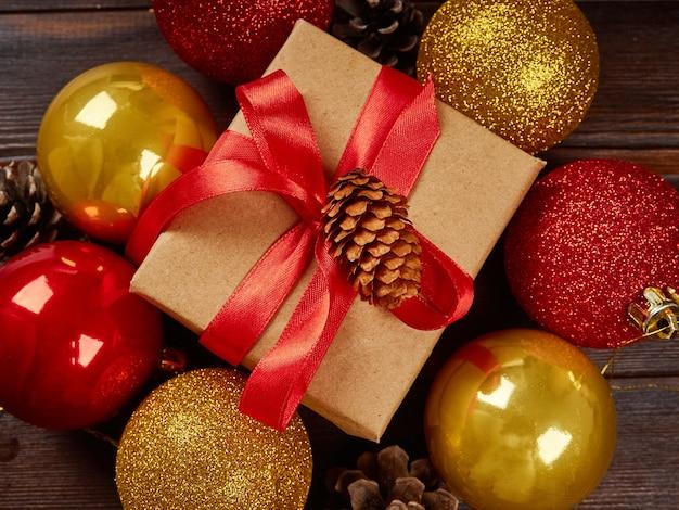 Composición navideña. bolas doradas brillantes, caja de regalo con cinta roja, piñas sobre una mesa de madera oscura. endecha plana, vista superior, primer plano