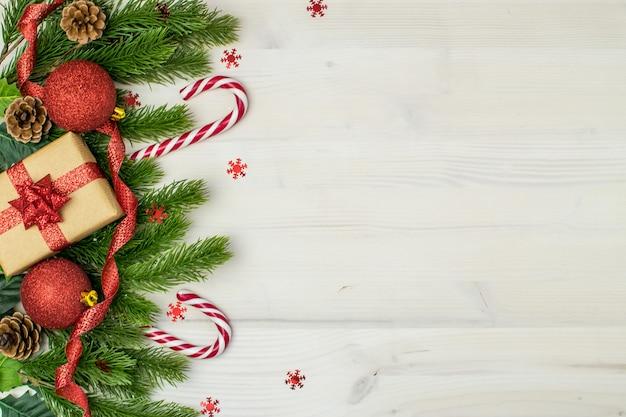 Composición navideña con bolas navideñas, regalos, muérdago, piñas, ramas de abeto, bastones de caramelo y copos de nieve sobre un fondo de madera clara