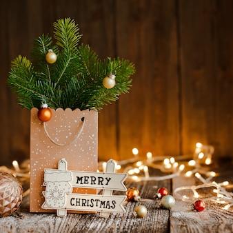 Composición navideña. bolsa de papel con y golpea ramas de abeto en madera marrón y luces bokeh.