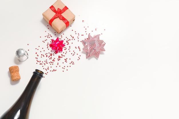 Composición navideña con botella de champán en blanco