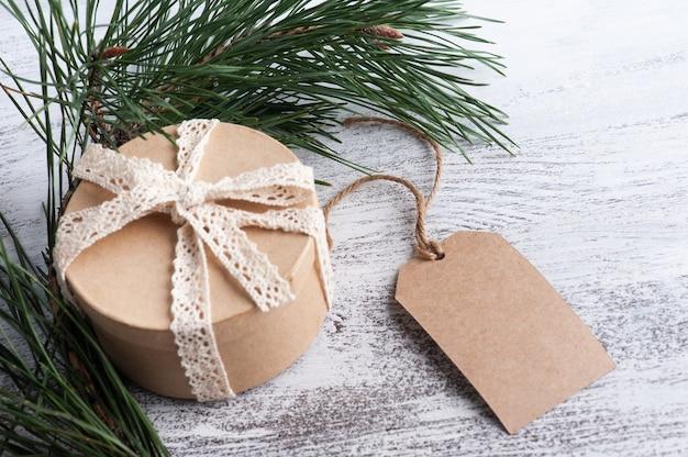 Composición navideña con caja de regalo, etiqueta kraft y ramas de pino, maqueta para saludo o publicidad