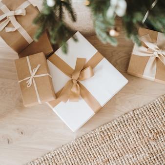 Composición navideña. cajas de regalo de vacaciones de invierno hechas a mano y ramas de abeto.