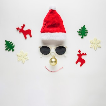 Composición navideña de cara hecha de sombrero y gafas de sol.