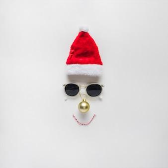 Composición navideña de cara de santa sombrero y gafas de sol.
