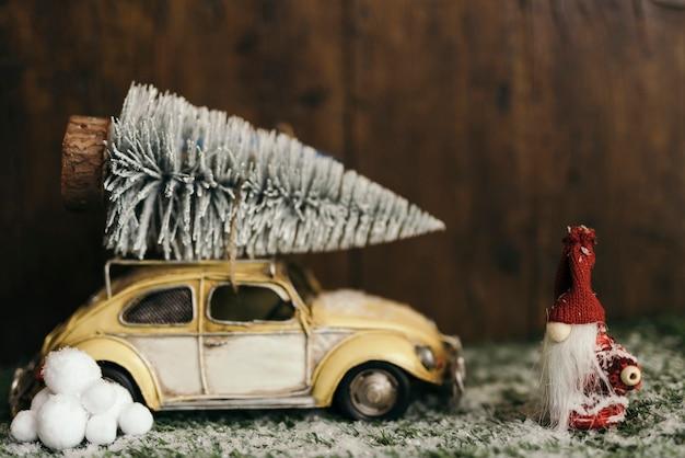 Composición navideña con un carro cargando un árbol de navidad.