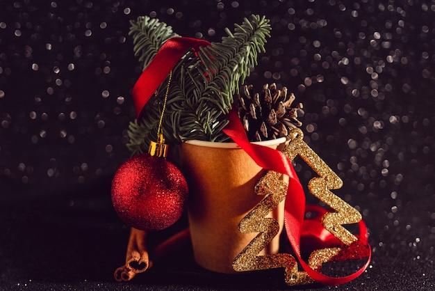 Composición navideña con conos de abeto en una taza de café de papel, elementos de decoración navideña