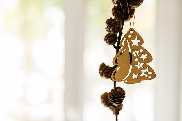 Composición navideña. conos de pino con adornos navideños de madera en ramas sobre fondo claro.