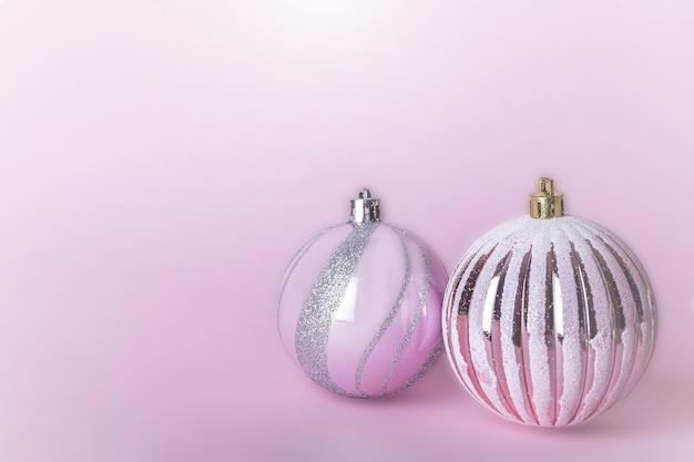 Composición navideña. dos bolas de navidad rosa, bolas brillantes colgando sobre fondo pastel