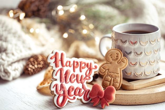 Composición navideña con galletas de jengibre artesanales glaseadas con deseos de feliz año nuevo. concepto de comodidad de invierno en casa.