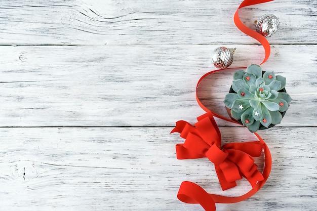 Composición navideña, maqueta con suculenta planta verde, lazo rojo y plata navideña.