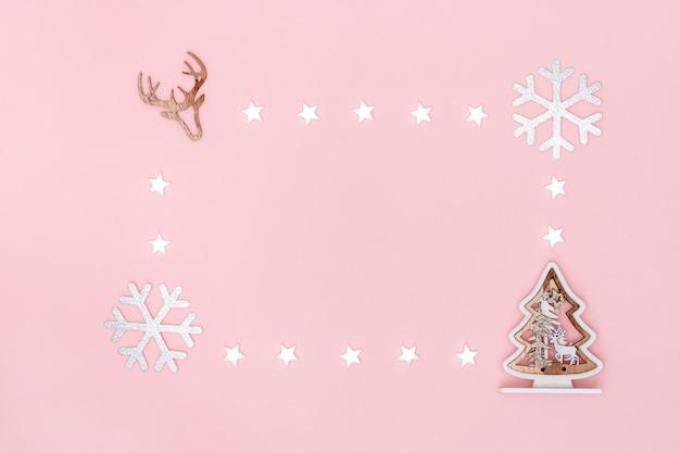 Composición navideña. marco de estrellas blancas, copos de nieve, árbol de navidad y símbolo de ciervo sobre fondo de papel rosa pastel. vista superior, plano, copia espacio.