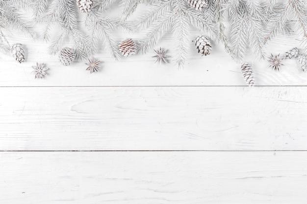 Composición navideña. marco hecho de ramas de abeto sobre fondo blanco de madera