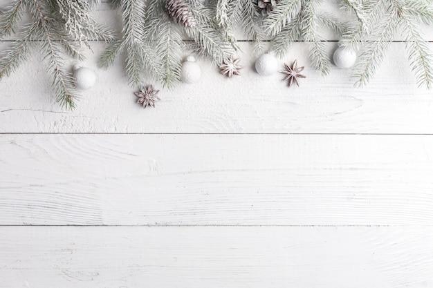 Composición navideña con marco de ramas de abeto, adornos navideños y piñas. vista plana, vista superior