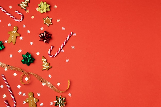 Composición navideña plana, pan de jengibre, cortador de galletas, bastón de caramelo, naranja seca, adornos y piña en rojo