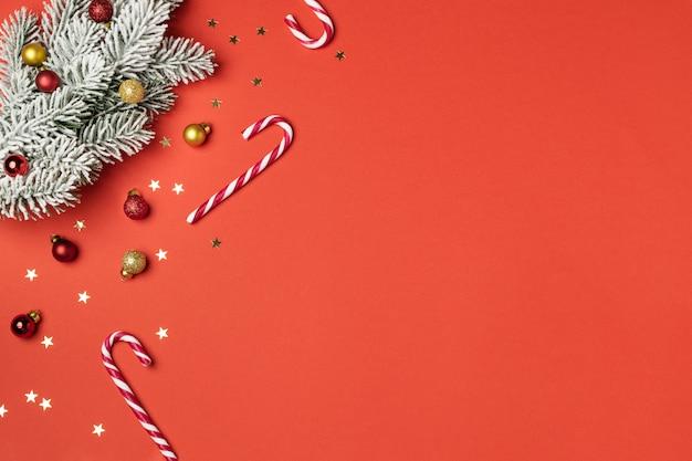 Composición navideña en plano, bastón de caramelo, rama de abeto y adornos en rojo