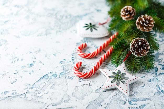 Composición navideña con rama de abeto, adornos navideños, bastones de caramelo