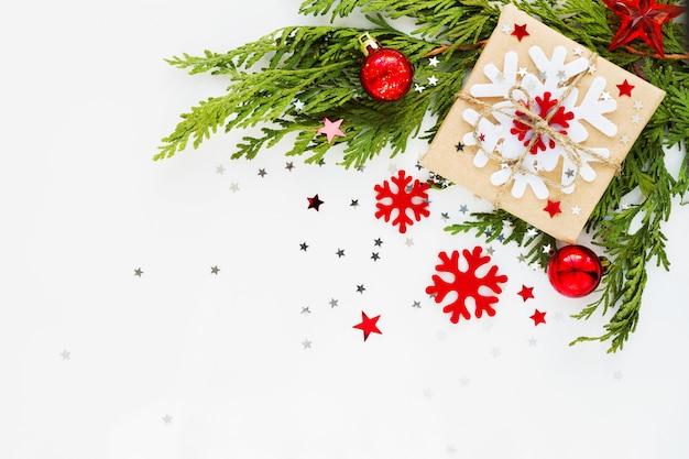 Composición navideña con rama de abeto, decoraciones y presente