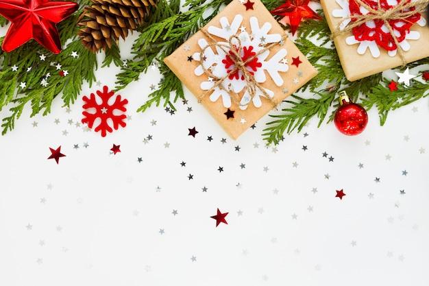 Composición navideña con rama de abeto, decoraciones y regalos