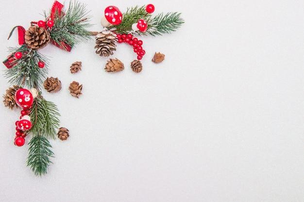 Composición navideña. ramas de abeto, adornos rojos sobre fondo blanco.