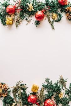 Composición navideña de ramas de abeto con adornos rojos.