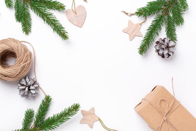 Composición navideña con ramas de abeto, caja de regalo y decoración natural sobre fondo blanco.
