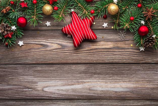 Composición navideña. ramas de abeto, cajas de regalo, adornos, piñas sobre fondo de madera