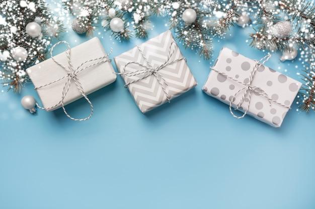 Composición navideña con ramas de abeto y cajas de regalo blancas