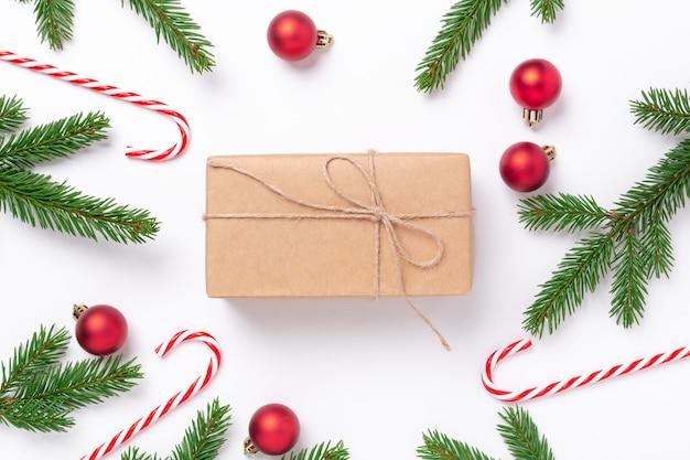 Composición navideña con ramas de abeto, decoración y caja actual sobre fondo blanco.