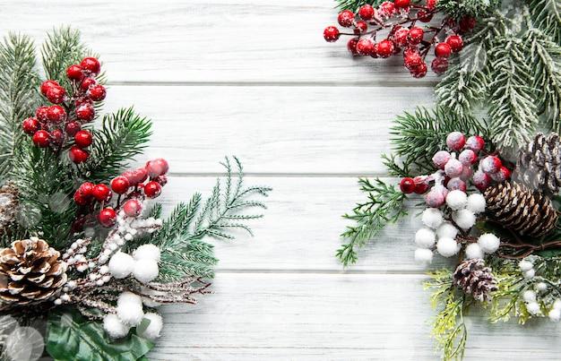 Composición navideña con ramas de abeto nevado sobre fondo blanco de madera