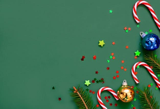 Composición navideña de ramas de árboles, bastones dulces, bolas navideñas, estrellas en un verde