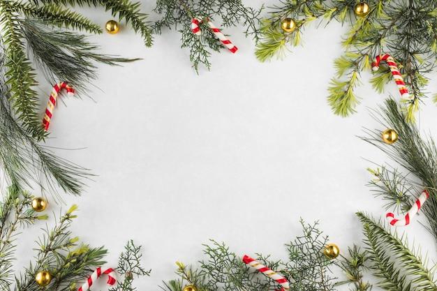 Composición navideña de ramas con bastones de caramelo.