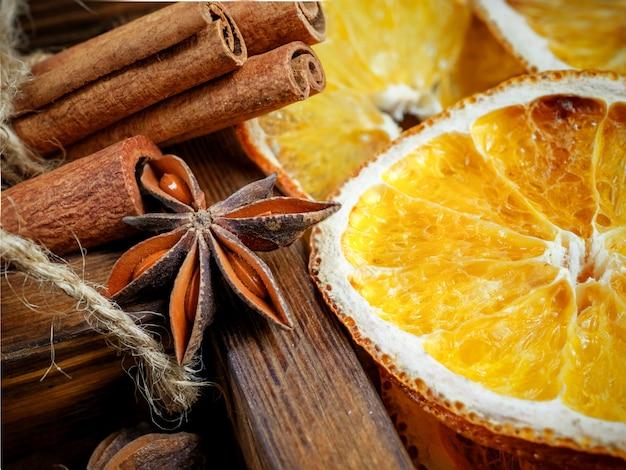Composición navideña con ramas y naranjas secas con palitos de canela