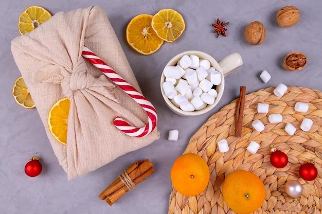 Composición navideña con un regalo estilo furoshiki, una taza de cacao y malvaviscos.